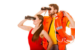 Lifeguards with ring buoy and life vest. Lifeguards with ring buoy lifebuoy and life vest jacket looking through binoculars. Man and women supervising swimming royalty free stock photography