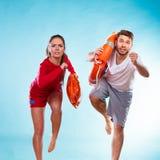 Lifeguards running with equipment Stock Photos