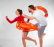 Lifeguards running with equipment Stock Images