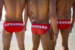 Lifeguards. Three young lifeguards on the beach looking at the sea Stock Photo