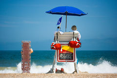 Lifeguards watching beach. Two young men beach lifeguards watch people swimming in the blue ocean with waves crashing on a sandy beach. Room for text stock images