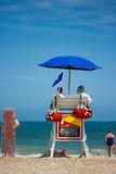 Lifeguards watching beach. Two young men beach lifeguards watch people swimming in the blue ocean with waves crashing on a sandy beach. Room for text stock photos