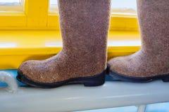 Lifehack voor het drogen van schoenen De gevoelde laarzen zijn op een warme batterij, verwarmend pijp in het dorpshuis stock afbeeldingen