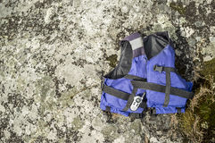 Lifejacket and radio are on the rocky shore. Lifejacket and radio are on the rocky coast, sunny spring day Royalty Free Stock Photo