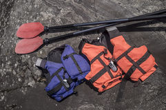 Lifejackets and radio are on the rocky coast, near lie oars. Royalty Free Stock Photo
