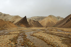 Lifeless orange rocks and a river during the sand storm, Iceland Stock Images