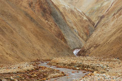 Lifeless orange and yellow hills and river running among them du. Marsian landscape with lifeless orange and yellow hills and river running among them during the Royalty Free Stock Images