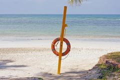 Life buoy in the empty beach of island Bintan, Indonesia. Lifesaver on the beach. A life ring sits on a post on the beach ready to save swimmers from drowning royalty free stock images