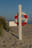 Lifesaver on beach. Lifesaver on sand beach with beach cabins huts Royalty Free Stock Photography