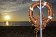 Lifesaver buoyancy aid on beach at sunrise. Clear view of a lifesaver buoyancy aid at sunrise. As the day begins it is poignant that the beach will fill and the Royalty Free Stock Image