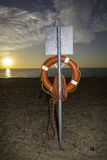 Lifesaver buoyancy aid at sunrise. Clear view of a lifesaver buoyancy aid at sunrise. As the day begins it is poignant that the beach will fill and the aid could Royalty Free Stock Photography