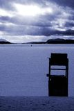 Lifesaver chair in winter. With sun through clouds and man ice fishing stock images
