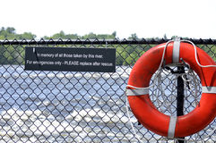 Lifesaver on a fence with commemorative sign text Stock Images