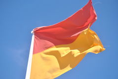 Lifesaver flag. Against a blue sky blowing in the wind Stock Photo