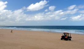 Lifesaver som kör barnvagnen på stranden Royaltyfri Fotografi