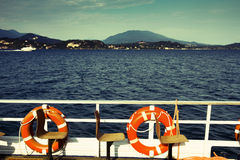 Lifesavers and seats. View of empty seats and lifesavers on a boat traveling on the Lago Maggiore in north of Italy, overlooking the beautiful landscape with the Stock Photos