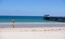 Lifesaving at Henley Beach. Photograph taken at Henley Beach featuring the jetty and a surf-lifesaver setting up the swimming flags for the day (Adelaide royalty free stock photo