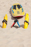 Lifesaving raft, floation devices and swimming fins on beach Royalty Free Stock Photography