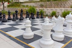 Lifesize Chess board at a hotel. Lifesize chess pieces on a board outside at a hotel pool side stock photo