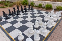 Lifesize Chess board at a hotel. Lifesize chess pieces on a board outside at a hotel pool side stock image