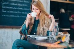 Lifestule de consumición del fondo de la taza de café de la mujer rubia joven Imágenes de archivo libres de regalías
