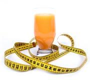 Lifestyle. Orange juice and measuring tape on white background Royalty Free Stock Image