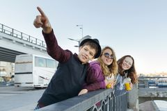 Lifestyle of adolescents, boy and two teen girls are walking in the city. Laughing, talking children eating street food, having. Fun. Background of the river royalty free stock photography