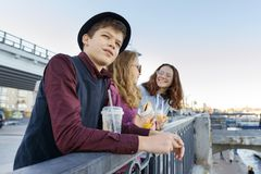 Lifestyle of adolescents, boy and two teen girls are walking in the city. Laughing, talking children eating street food, having. Fun. Background of the river stock images