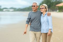 Lifestyle asian senior couple happy walking and relax on the beach.  Tourism elderly family travel leisure and activity after reti