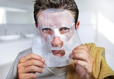 Young scared and surprised man at home using beauty paper facial mask cleansing doing anti aging facial treatment looking himself stock photos