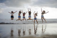 Lifestyle beach portrait of young group of Asian Korean and Chinese women , happy and attractive girlfriends enjoying Summer holid royalty free stock photography