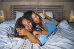 Lifestyle bedroom portrait of happy Asian woman at home posing with her beautiful 8 years old daughter in bed smiling playful stock photo