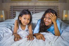 Lifestyle bedroom portrait of happy Asian woman at home posing with her beautiful 8 years old daughter in bed smiling playful stock image