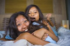 Lifestyle bedroom portrait of happy Asian woman at home posing with her beautiful 8 years old daughter in bed smiling playful royalty free stock photos