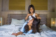 Lifestyle bedroom portrait of happy Asian woman at home playing with little daughter in bed cuddling and laughing cheerful in royalty free stock photo