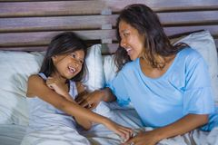 Lifestyle bedroom portrait of happy Asian woman at home playing with little daughter in bed cuddling and laughing cheerful in royalty free stock image