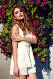Lifestyle blond model girl in casual cloth near flowers with pink lips Royalty Free Stock Photos