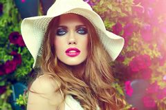 Lifestyle blond model girl in casual cloth near flowers with pink lips Stock Photo