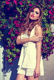 Lifestyle blond model girl in casual cloth near flowers with pink lips Stock Image