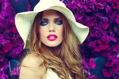 Lifestyle blond model girl in hat near flowers with pink lips Royalty Free Stock Photo