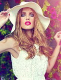 Lifestyle blond model girl in hat near flowers with pink lips Stock Images