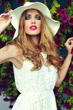 Lifestyle blond model girl in hat near flowers with pink lips Stock Photos