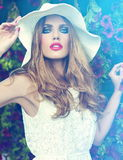 Lifestyle blond model girl in hat near flowers with pink lips Royalty Free Stock Photos