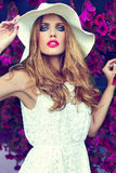 Lifestyle blond model girl in hat near flowers with pink lips Royalty Free Stock Images