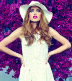 Lifestyle blond model girl in hat near flowers with pink lips Royalty Free Stock Photography