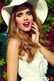 Lifestyle blond model girl in hat near flowers with pink lips Stock Photography