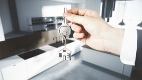 Lifestyle and buy concept. Businessman hand holding abstract key with house keychain on blurry kitchen interior background. Lifestyle and buy concept. 3D Stock Photo