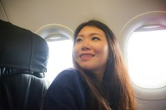 Lifestyle candid portrait of young happy and beautiful Asian Chinese woman traveling for holidays inside airplane cabin excited on stock images