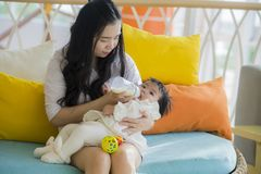 Lifestyle candid portrait of young happy and sweet Asian Chinese woman feeding her beautiful baby girl with formula bottle at stock photo