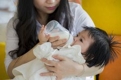 Lifestyle candid portrait of young happy and sweet Asian Japanese woman feeding her beautiful baby girl with formula bottle at royalty free stock image